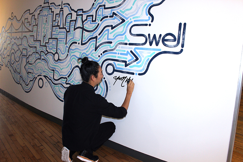 Yoon Hyup talks with S'well water bottles to discuss his latest mural at S'well headquarters